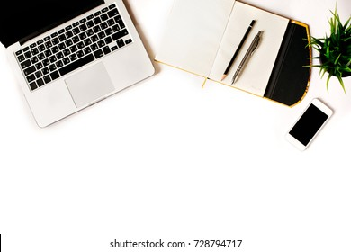 Modern minimalistic work place. White office desk table with laptop, smart phone, office plant, notebook, pen and pencil. Top view with copy space, flat lay, square crop