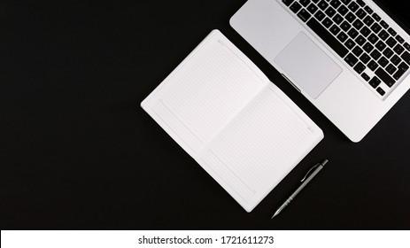 Moderner minimalistischer Arbeitsbereich mit Laptop, geöffnetes schwarzes Ledernotebook und Stift auf dem schwarzen Schreibtisch. Flachbildschirm, Kopienraum, Draufsicht