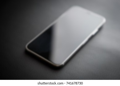 Modern mobile device like iPhone X model.New smartphone blur background.Out of focus cellphone with big infinity edge display.Touchscreen panel on black background