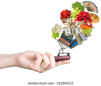 Modern mobile phone in the hand with lots of goods isolated on white (e-shopping concept)