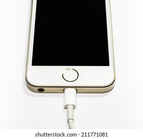 Modern mobile phone on charge. On a white background