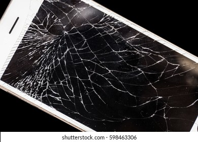 Modern mobile smart phone with broken cracked screen isolated on black background, close up.