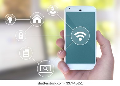 Modern mobile smart phone connecting to wifi automation apps in male hand with office laptop in bokeh style background