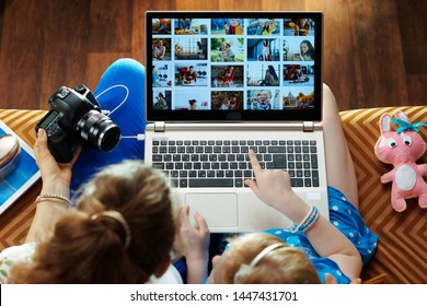 modern mother and child sitting on couch in the modern living room looks at photo collage while transferring photos from DSLR photo camera on a laptop.