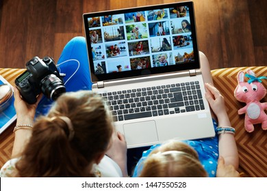 modern mother and child sitting on sofa in the modern living room viewing image library while transferring photos from DSLR photo camera on a laptop.