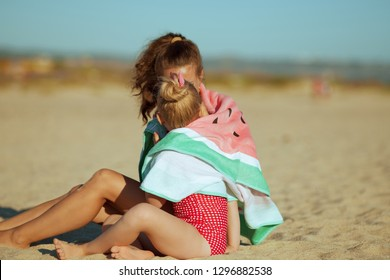 modern mother and daughter in beachwear on the beach in the evening wrapped in watermelon towel spending time. mother and daughter hugging sitting on sand. no face visible. blue sky.
