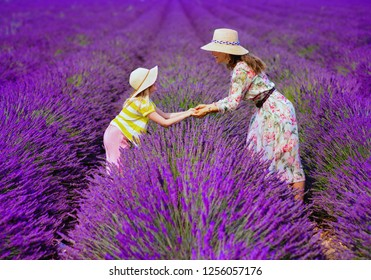 modern mother and daughter in lavender field in Provence, France stand holding hands. relaxed and calming looming lavender field in July or August is perfect place for family tourists