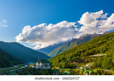 Modern mountain cottages with green roofs against the backdrop of a mountain valley covered with a green spring sun forest. Ski Resort at Caucasus Mountains, Krasnaya Polyana, Sochi, Russia.