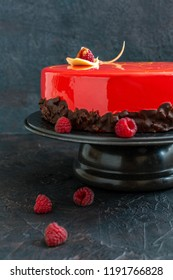 Modern mousse cake with red mirror glaze and decoration of white chocolate and raspberry on a textured dark background.