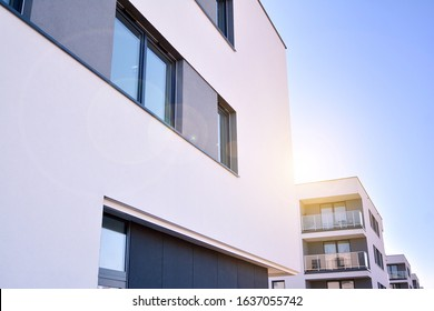 Modern multi story building being lit by the setting sun at afternoon. New apartment house residential building outdoor concept.