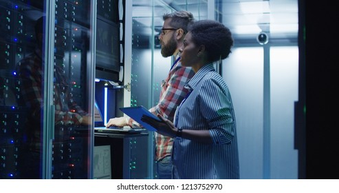 Modern multiethnic man and woman with tablet using laptop in server room while checking servers - Shutterstock ID 1213752970
