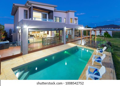 Modern multilevel house exterior with pool at dusk