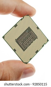 Modern multiple core CPU between male fingers on white
