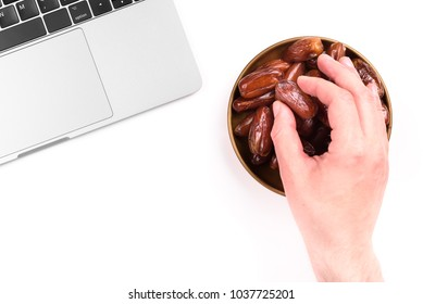 Modern muslim lifestyle. Holy month of Ramadan. A man's hand reaches out to a plate with dates near the laptop. White background.  Traditions and modernity concept.