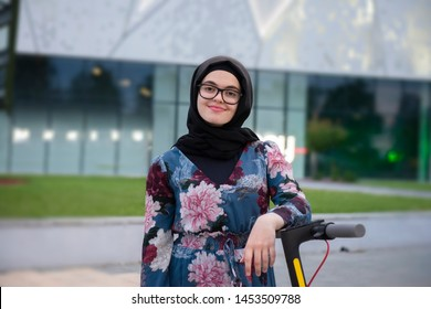 Modern muslim woman with a hijab rides e-scooter in front of a mall