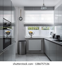Modern, narrow kitchen with window and gray furniture
