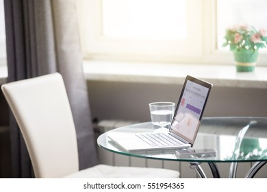 Modern neat comfortable organized working place, open laptop with calendar on the screen on a glass table, planning, stable freelancing job, setting your own schedule, start working at the morning