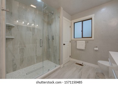 Modern new grey walls and white vanity bathroom interior with large walk-in shower with glass door.