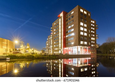 Modern new residential district in Leiden, The Netherlands, with apartment buildings reflected in the water at night