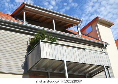 Modern new spandrel-braced Balconies with Hand Rails of high-grade Steel combined with varnished wooden Planks and sheltered Roof Balcony at the Front of a refurbished old residential Building
