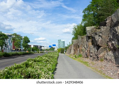 The modern new street of Turku with a roadway and a natural stone wall is a characteristic feature of this Finnish city. Turku City, Abo on a summer day in Finland