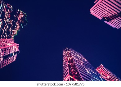 A modern night city. Skyscrapers with pink illumination