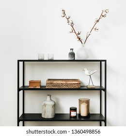Modern nordic interior design concept. Stylish rack with caskets, cotton branch, vase, candles and bird figurine at white wall.