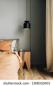 Modern Nordic Scandinavian interior design concept. Bedroom with bed, ginger bedcover, pillows, oak nightstand, designer pendant light, wooden floor. Elegant apartment for rent.