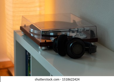 Modern nostalgic vinyl LP record player turntable with wireless headphones for listening to rock or jazz music or other sounds