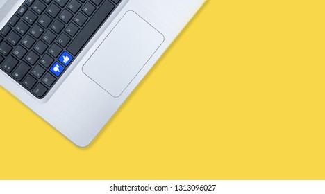 Modern notebook computer with blu like unlike keys on yellow background