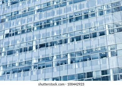 Modern office building with blue windows with reflections