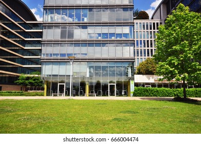 Modern office building in the city park. View of a business quarter on summer