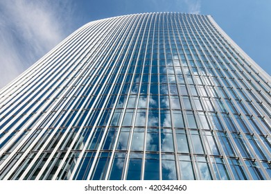 Modern office building. Clouds and building reflections on the glass of a curtain wall