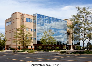 Modern Office Building with Glass – A modern office building covered with glass, reflecting the clouds on a beautiful day.