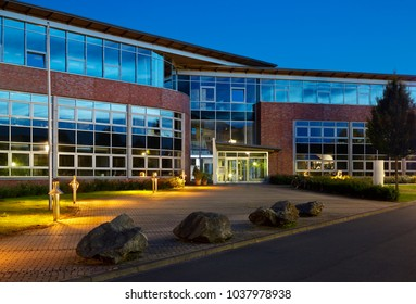 A modern office building with glass facades and illumination at blue hour.