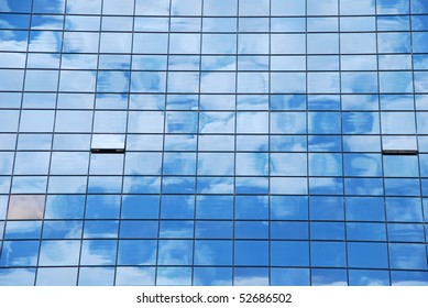 modern office building with glass pattern with clouds reflected