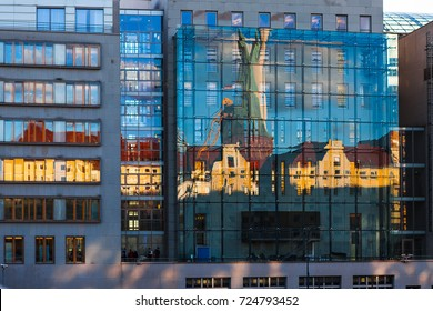 Modern office building with glass reflection of old Berlin color embankment buildings