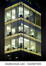 modern office building illuminated at night with geometric windows