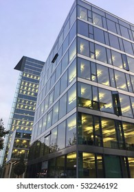 modern office building with lights on at dusk