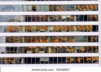 Modern office building at night. View of the interior workplaces in the office through the window.