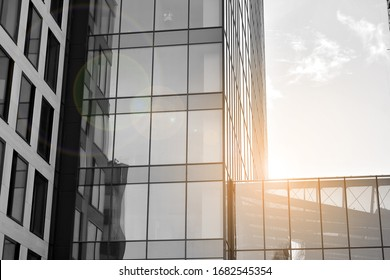 Modern office building wall made of steel and glass with blue sky. Glass surface with sunlight. Black and white.
