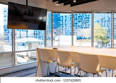 Modern office in building with wooden meeting corporate business table with television screen and chairs empty nobody