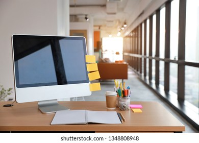 modern office with computer on wood desk, office supplies and coffee cup