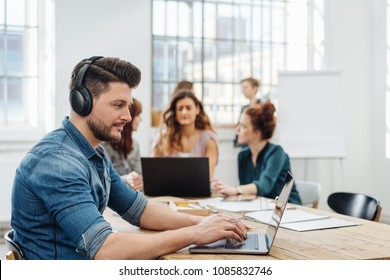 Modern office with a dedicated young business team working on paperwork and laptops seated around a table with focus to a young man wearing headphones typing on a laptop