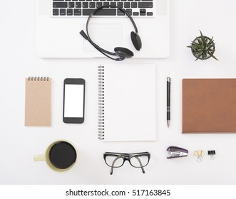 Modern Office desk with computer, notebook, headset, paper book, mobile phone and coffee cup.Top View table from above with copy space for input the text.