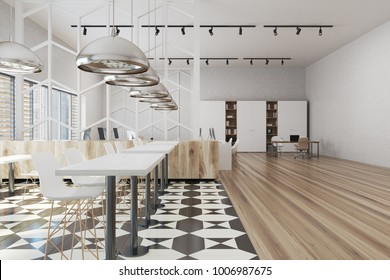Modern office interior with a checkered and wooden floor, large windows, and rows of computer tables. 3d rendering mock up