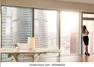 Modern office interior with desk and female silhouette standing back at full length window of business center, talking on phone, looking at cityscape, businesswoman having break at work after meeting