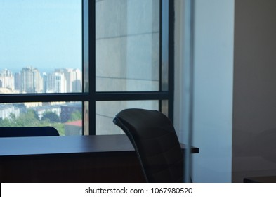 Modern office interior of large window with tables, phone,chairs and bookcases. Nobody