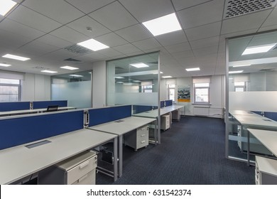Modern office interior with multiple open-plan work stations at long desks