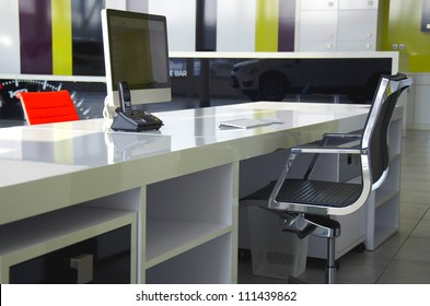 Modern office interior with red chairs and white furniture